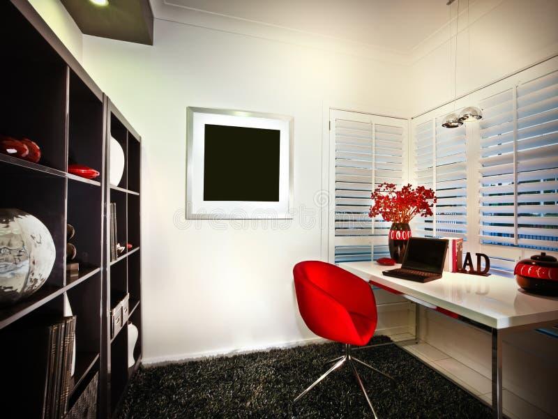 Un cuarto de estudio con la ventana y los estantes de librería y un ordenador portátil colocado encendido fotografía de archivo