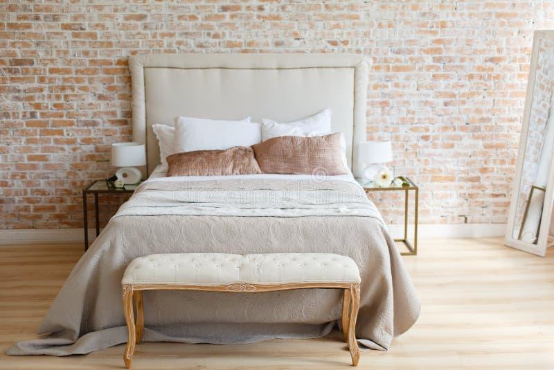 Un cuarto en montante ligero del desván con la pared de ladrillo y muebles ligeros fotos de archivo