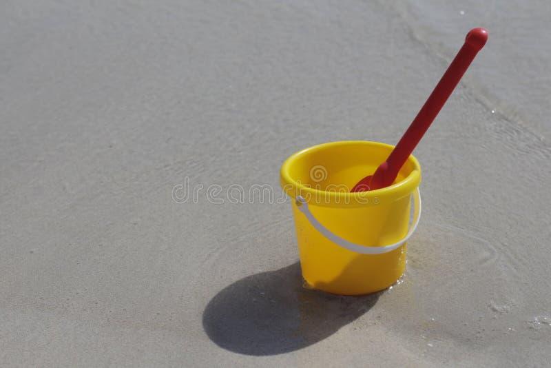 Un cubo amarillo del bebé y un soporte rojo de la pala en la arena por el mar fotografía de archivo libre de regalías