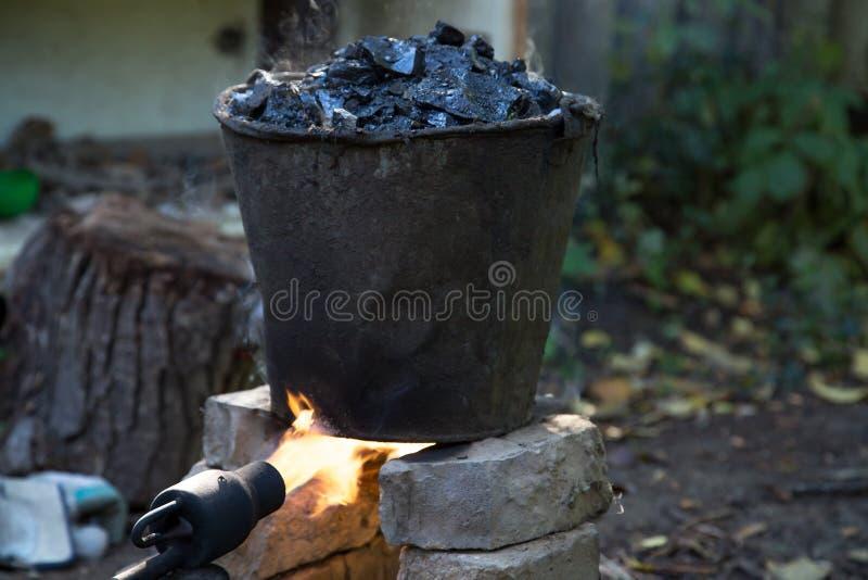Un cubo de alquitrán en el fuego, para las reparaciones del tejado imagenes de archivo