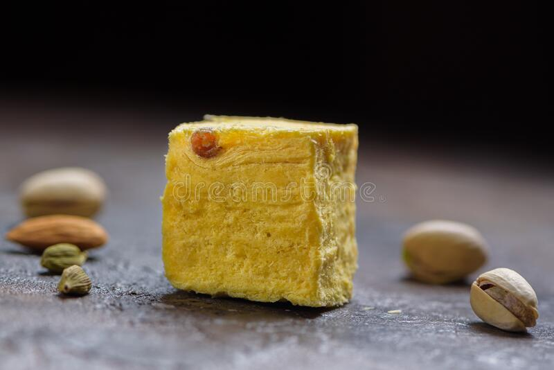 Un cubo de postre papdi soan, granos cardamomo, pistachos y almendros en la superficie de la cocina de hormigón imágenes de archivo libres de regalías