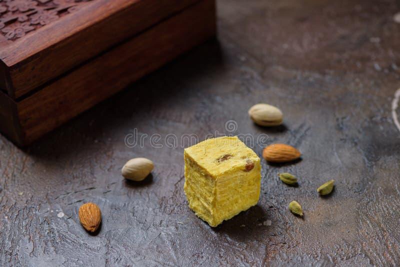 Un cubo de postre papdi soan, granos cardamomo, pistachos y almendros en la superficie de la cocina de hormigón fotos de archivo libres de regalías