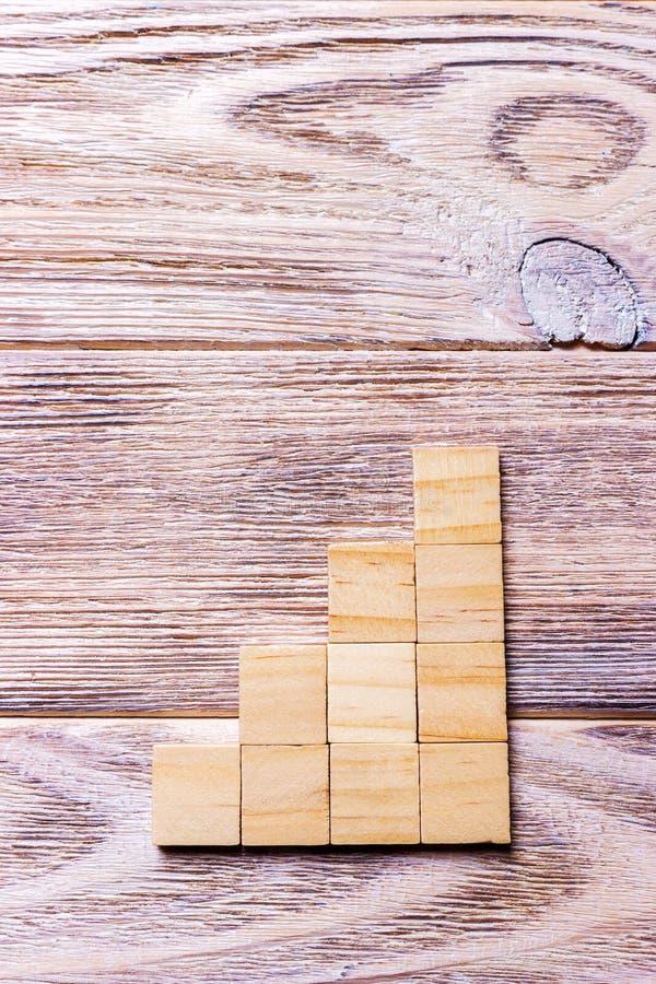 Un cubo di legno dei blocchi sopra fondo strutturato di legno nero con lo spazio della copia per aggiunge il titolo di testo di p fotografie stock