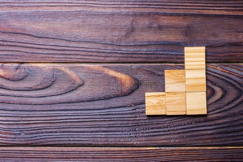 Un cubo di legno dei blocchi sopra fondo strutturato di legno nero con lo spazio della copia per aggiunge il titolo di testo di p fotografia stock