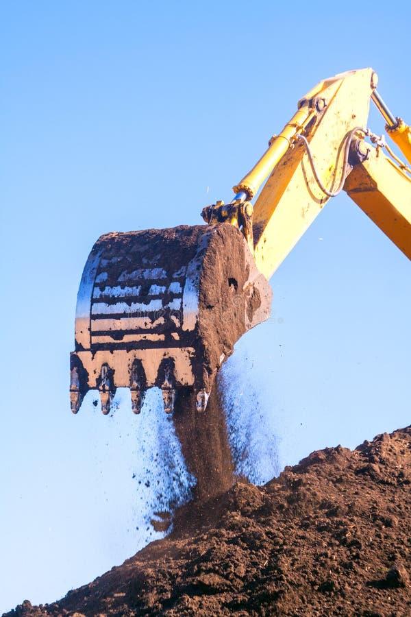 Un cubo grande del excavador del hierro recoge y vierte los escombros y las piedras de la arena en una mina en el emplazamiento d imagen de archivo