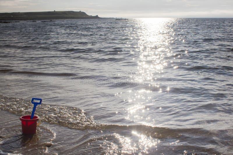 Un cubo y una espada en una playa arenosa en Sutherland, Escocia , foto de archivo