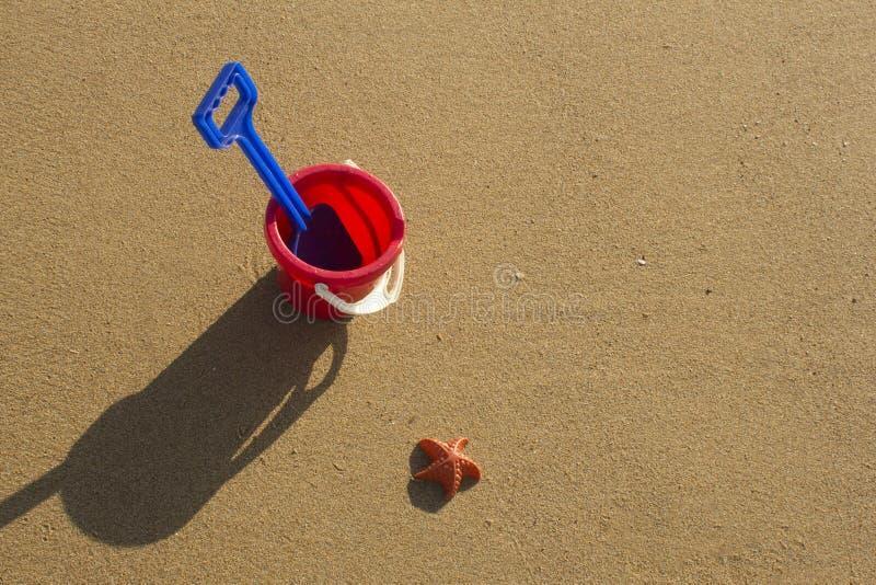 Un cubo y una espada en una playa arenosa en Sutherland, Escocia foto de archivo
