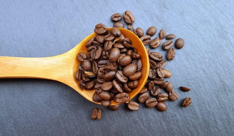 Un cucchiaio di legno con i chicchi di caffè fotografia stock
