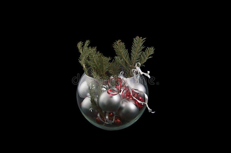 Un cuenco cristalino llenó de la bola de plata y de los wi rojos de los ornamentos de la bola fotos de archivo