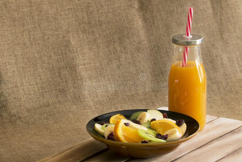 Un cuenco de ensalada de fruta al lado de una botella de jugo del mango foto de archivo libre de regalías