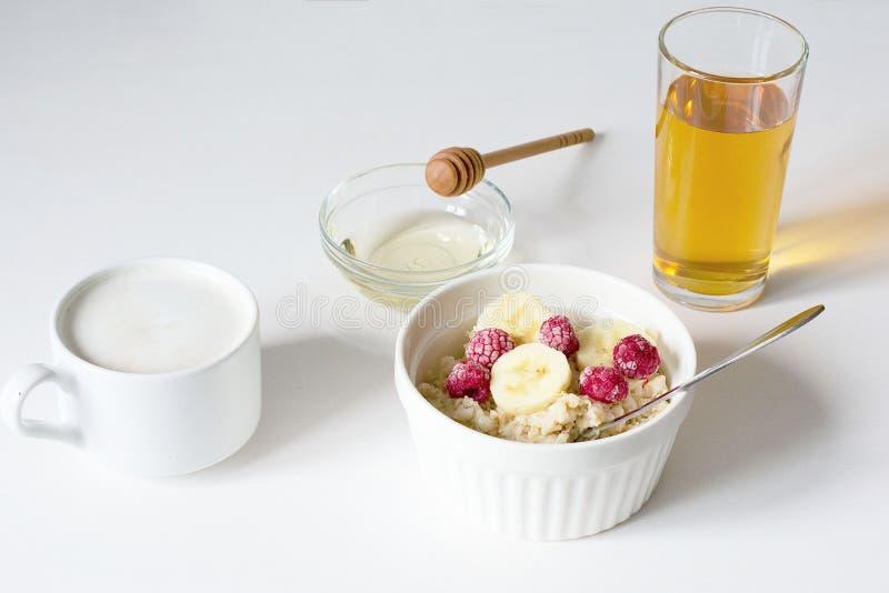 Un cuenco de harina de avena en un fondo blanco Desayuno sano fotografía de archivo