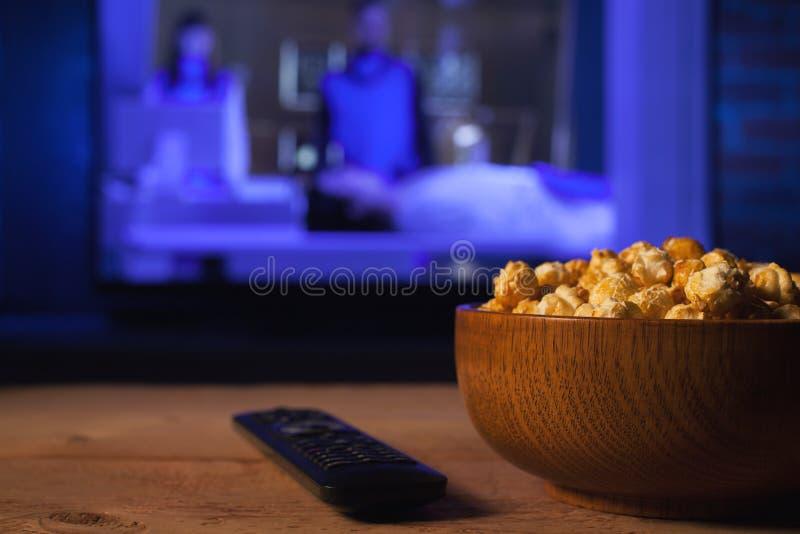 Un cuenco de madera de palomitas y teledirigido en el fondo que la TV trabaja Igualación acogedora mirando una película o serie t foto de archivo