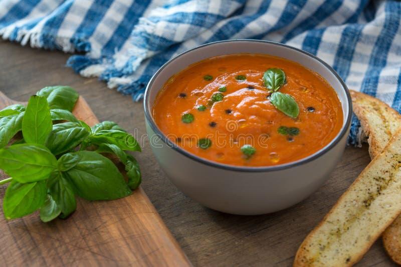 Un cuenco de sopa fresca del tomate en el cuenco de cerámica blanco, adornado con albahaca, los cuscurrones, el condimento y una  foto de archivo libre de regalías