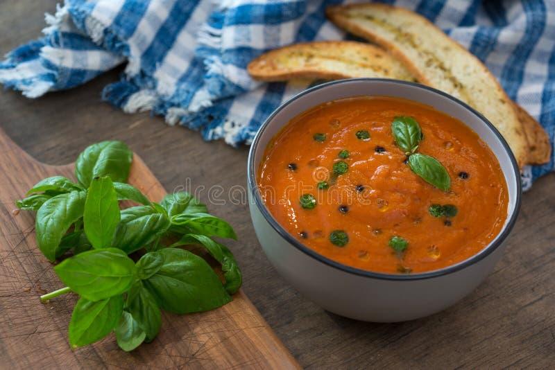 Un cuenco de sopa fresca del tomate en el cuenco de cerámica blanco, adornado con albahaca, los cuscurrones, el condimento y una  imagen de archivo