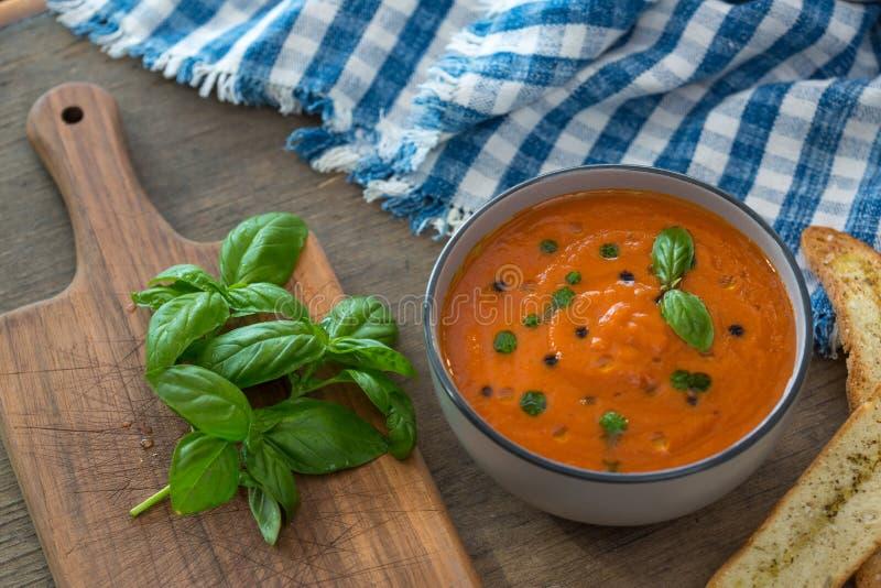 Un cuenco de sopa fresca del tomate en el cuenco de cerámica blanco, adornado con albahaca, los cuscurrones, el condimento y una  imágenes de archivo libres de regalías