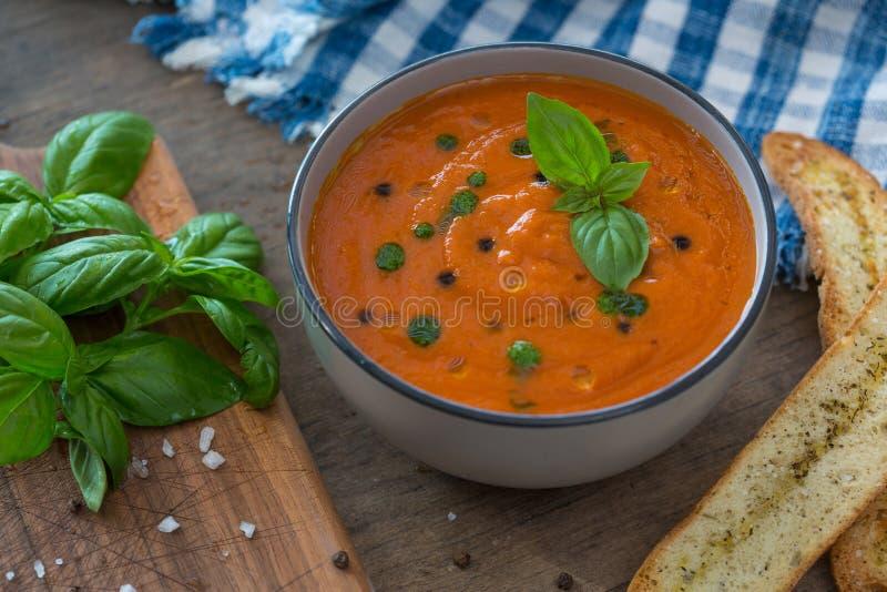 Un cuenco de sopa fresca del tomate en el cuenco de cerámica blanco, adornado con albahaca, los cuscurrones, el condimento y una  imagenes de archivo
