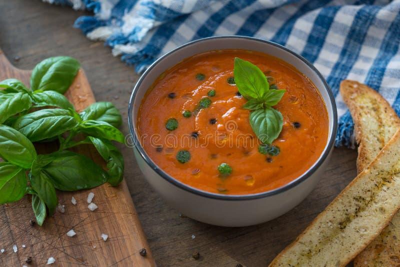 Un cuenco de sopa fresca del tomate en el cuenco de cerámica blanco, adornado con albahaca, los cuscurrones, el condimento y una  fotografía de archivo