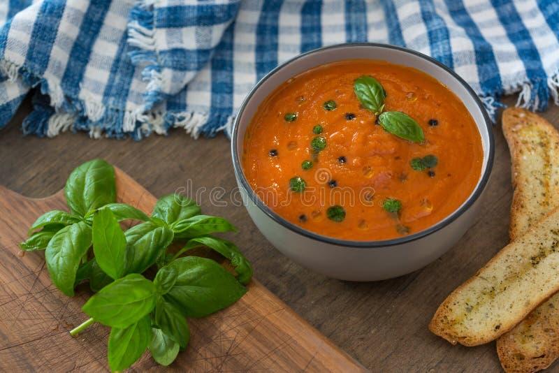 Un cuenco de sopa fresca del tomate en el cuenco de cerámica blanco, adornado con albahaca, los cuscurrones, el condimento y una  fotos de archivo