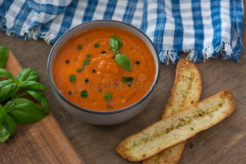 Un cuenco de sopa fresca del tomate en el cuenco de cerámica blanco, adornado con albahaca, los cuscurrones, el condimento y una  fotografía de archivo libre de regalías