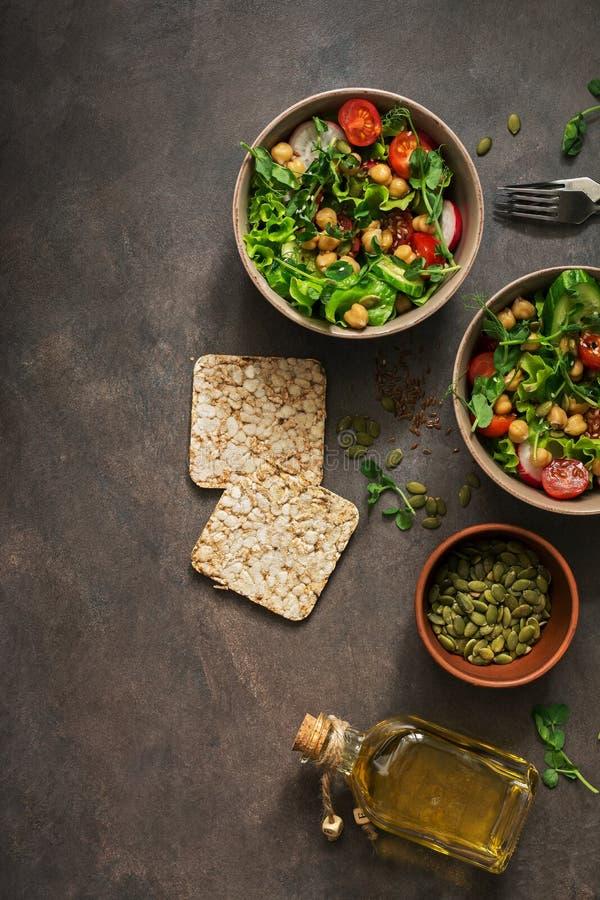 Un cuenco de vegano y ensalada vegetariana y garbanzos de las verduras frescas en un fondo oscuro Visi?n superior, espacio de la  fotografía de archivo