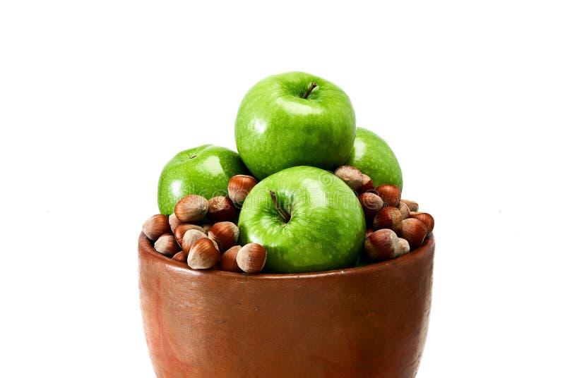 Un cuenco marrón de la loza de barro llenado de las manzanas verdes del granny smith y de las avellanas marrones aisladas en el f imagen de archivo libre de regalías