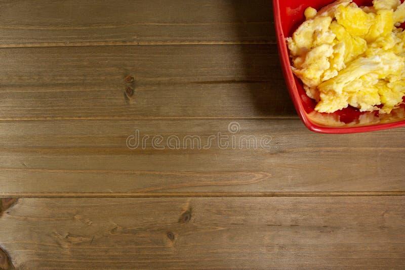 Un cuenco rojo con los huevos revueltos para el desayuno en la tabla de cocina que espera para ser comido fotografía de archivo libre de regalías