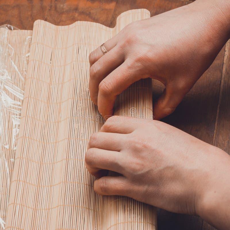 Un cuisinier féminin prépare des sushi dans la cuisine et enveloppe une lettre au nori dans le petit pain photographie stock