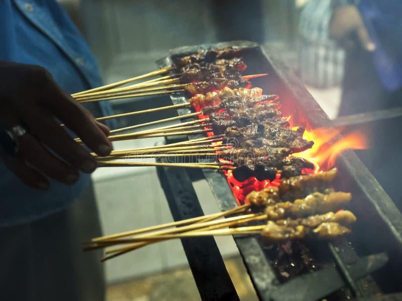 Un cuisinier prépare des brochettes de viande sur une rue dans le kuta, Bali images libres de droits