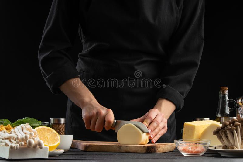 Un cuoco professionista prepara un'insalata italiana fresca e salutare affettando il formaggio di mazzarella, alimenti biologici  fotografia stock libera da diritti