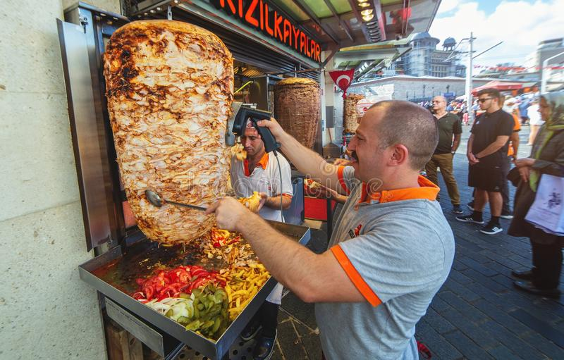 Un cuoco unico che taglia kebab turco tradizionale di Doner dell'alimento immagine stock libera da diritti