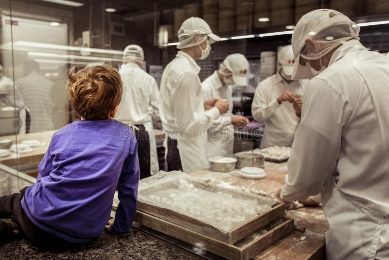 Un cuoco unico di sorveglianza della giovane finestra del ragazzo che produce gli gnocchi cinesi immagini stock libere da diritti
