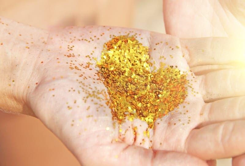 Un cuore brillante dorato si trova nelle mani della ragazza Cuore nelle palme Cuore dorato fotografie stock