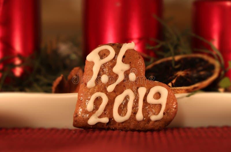 Un cuore casalingo del pan di zenzero coperto di glassa bianca e di desiderio a voi del PF 2019 Nel candeliere di natale del fond fotografie stock