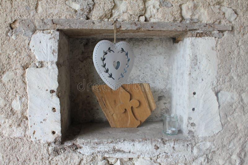 Un cuore che appende in un foro in una parete di pietra fotografia stock libera da diritti