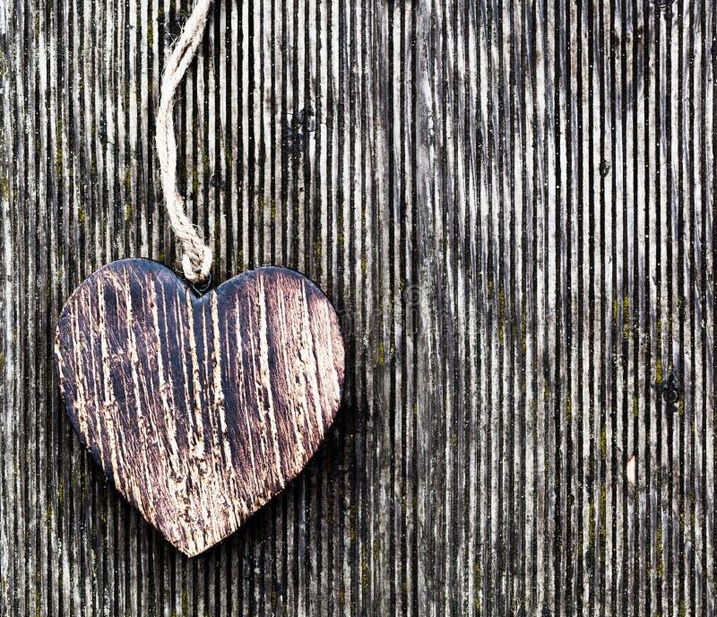 Un cuore d'annata di legno sulle plance di legno di lerciume. Amore fotografia stock