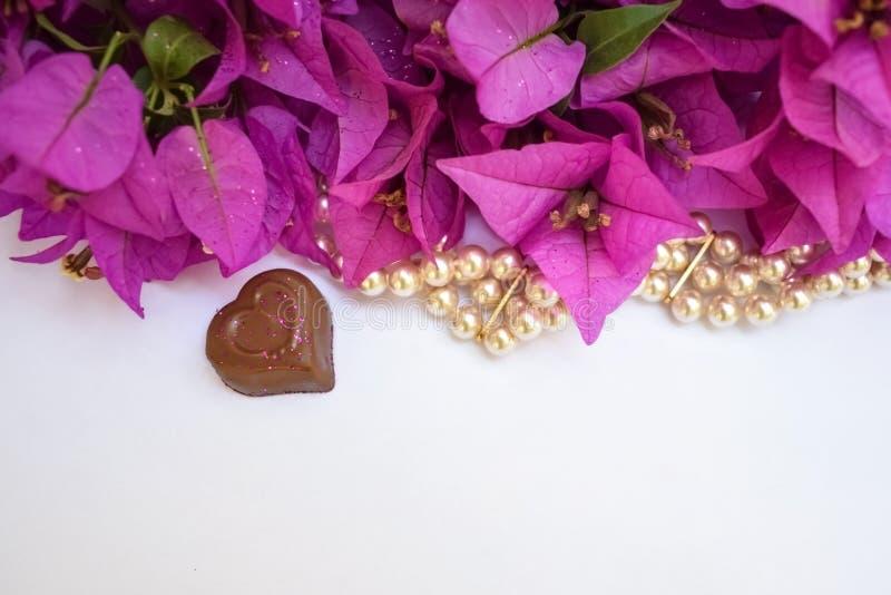 Un cuore del cioccolato, perle e fiori rosa luminosi immagini stock libere da diritti