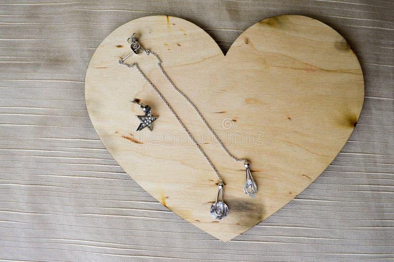 Un cuore di legno per il giorno del ` s del biglietto di S. Valentino con gli orecchini d'argento con i diamanti, pietre preziose fotografie stock libere da diritti
