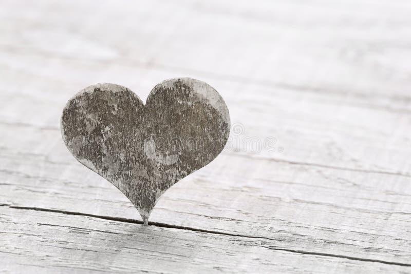 Un cuore di legno su un fondo per una cartolina d'auguri. immagine stock