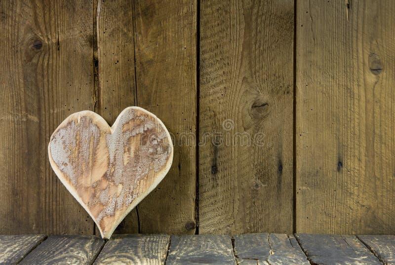 Un cuore di legno su un vecchio fondo rustico per una cartolina d'auguri. fotografia stock libera da diritti