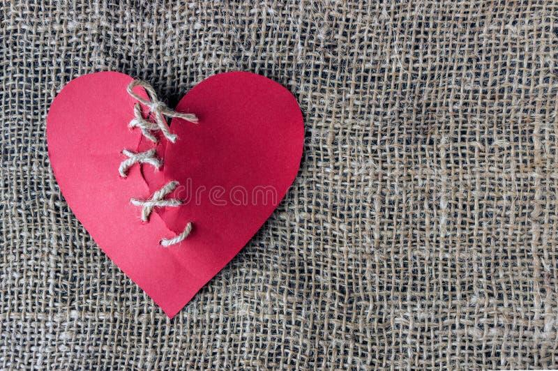 Un cuore rosso rotto Filo cucito Il concetto del divorzio, separat immagini stock