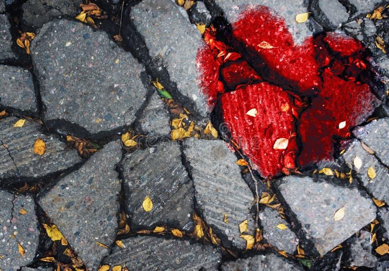 Un cuore rotto sull'asfalto Il concetto di amore infelice, malinteso, tristezza, felicità fotografie stock