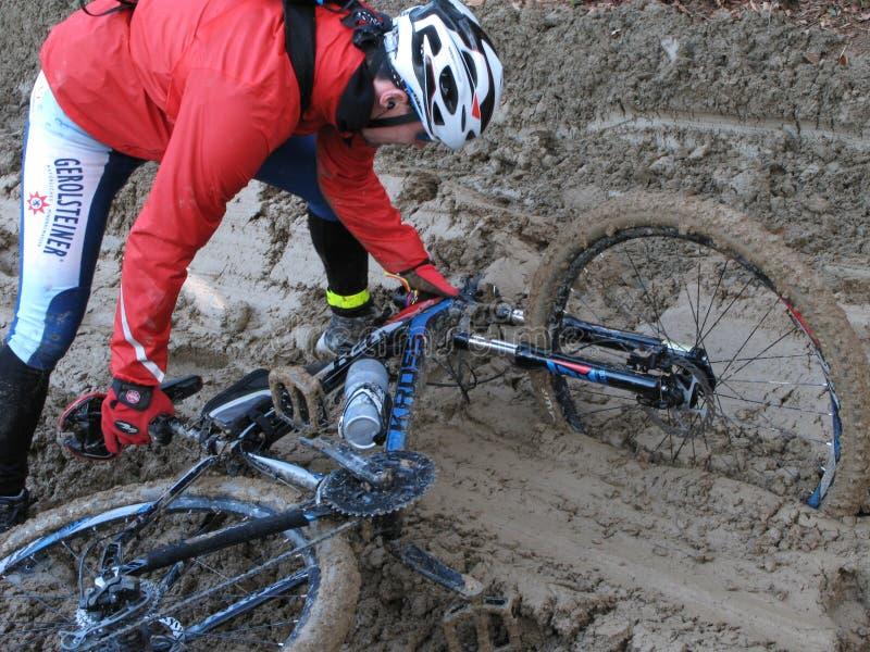 Un cycliste est tombé vélo dans la boue photographie stock libre de droits