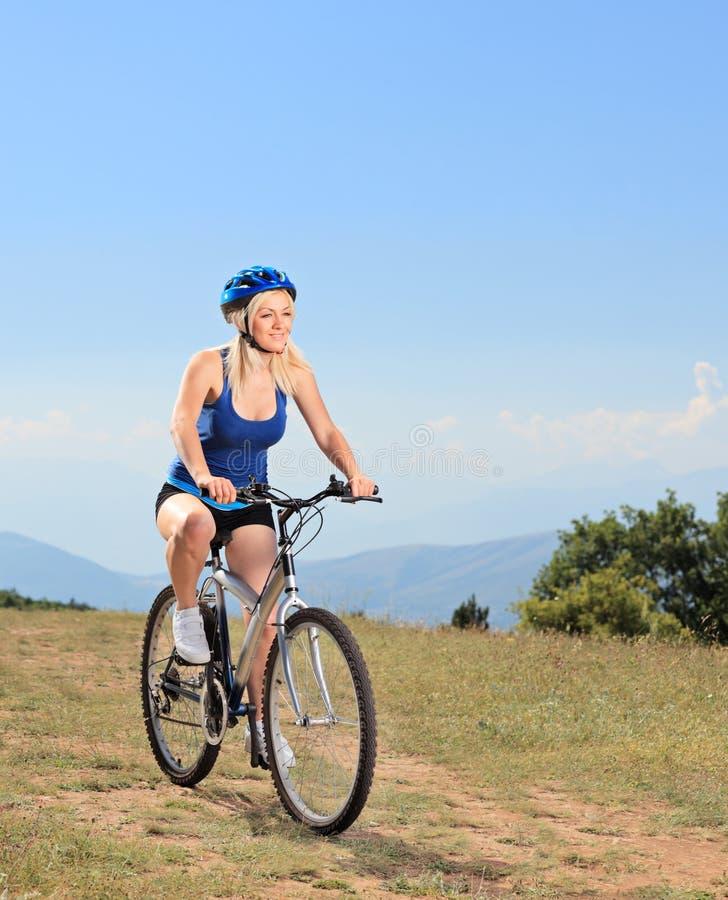 Un cycliste féminin faisant du vélo un vélo de montagne photos stock