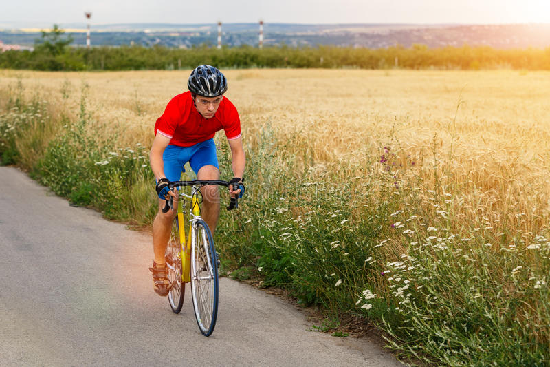 Un cycliste monte sur une bicyclette de route le long du champ Lueur de Sun image stock