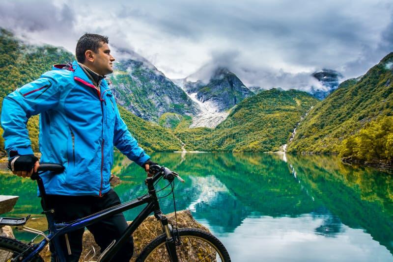 Un cycliste se tient à côté d'aller à vélo sur le fond un amazin photo stock
