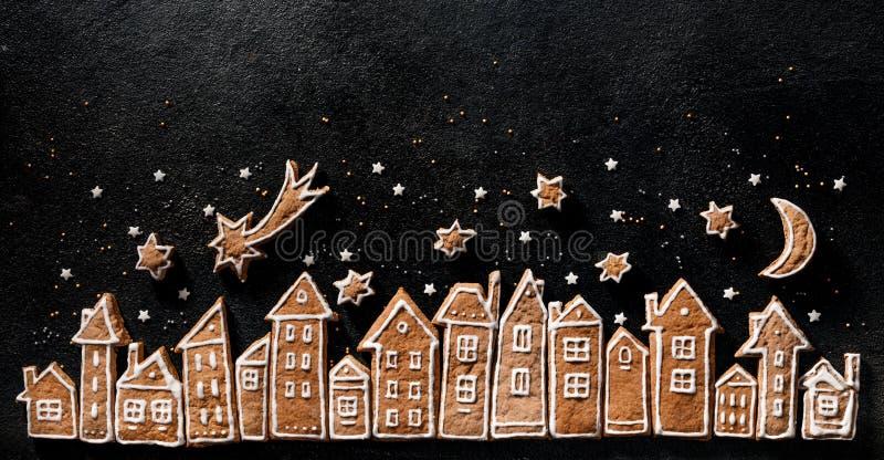 Un décor de Noël, des biscuits en pain d'épice des maisons et des stars en pain d'épice sur fond noir images stock