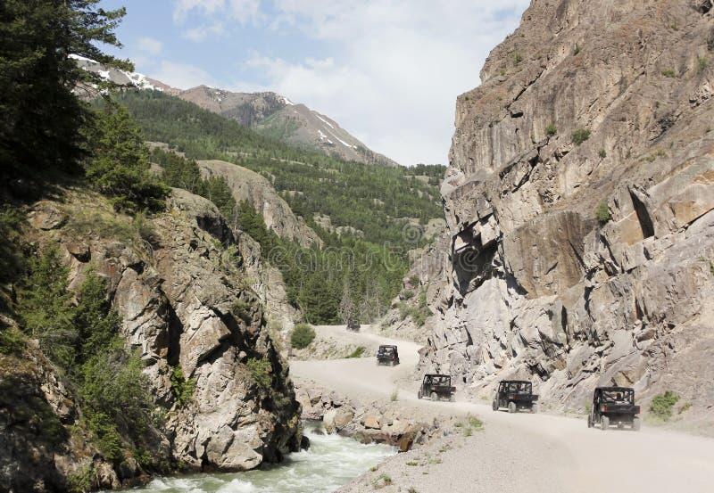 Un défilé d'ATVs sur le chemin détourné alpin de Backcountry de boucle images libres de droits