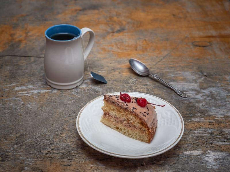 Un déjeuner doux de thé et une tranche de gâteau fait maison sur une vieille table rustique photo libre de droits