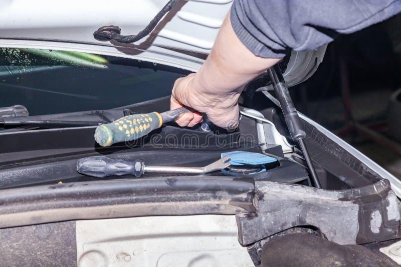 Un dépanneur de voiture dévisse des parties avec une clé avec une poignée verte dans le compartiment réacteur dans une réparation image libre de droits