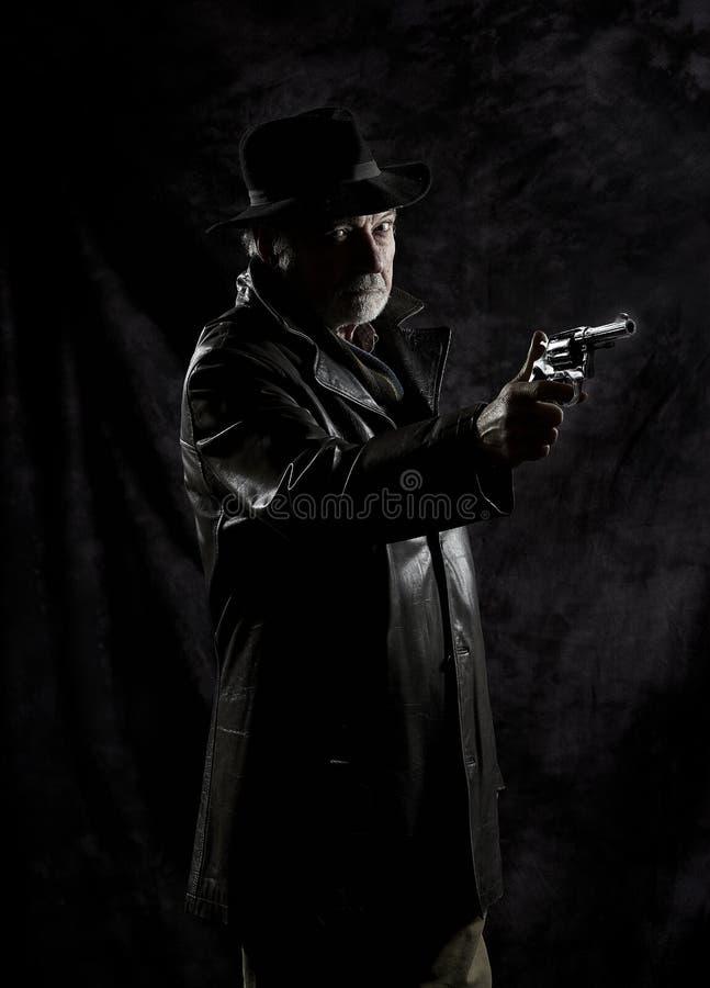 Un détective privé avec un revolver devant un contexte noir photos libres de droits